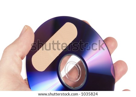 A compact disk or dvd with a bandage on it. Isolated on white with clipping path. - stock photo