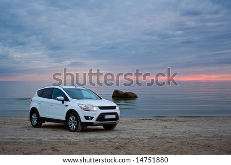 A compact SUV on a beach. Sunset.
