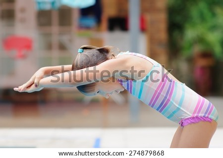 A competitive child, little preschool or school age girl, getting ready to jump into the water of the pool outdoors on a summer day.