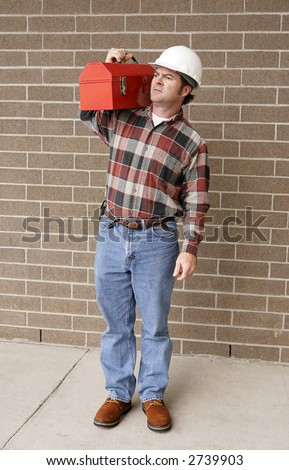 A complete, full-length view of a working man with his hard hat and toolbox. - stock photo