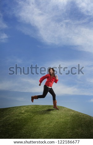 A composite of an enthusiastic girl running happily on a grass hill with a blue sky.