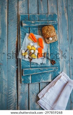 A composition of mozzarella balls, papaya and pineapple sliced served on blue vintage chalkboard from above. Rustic style. - stock photo