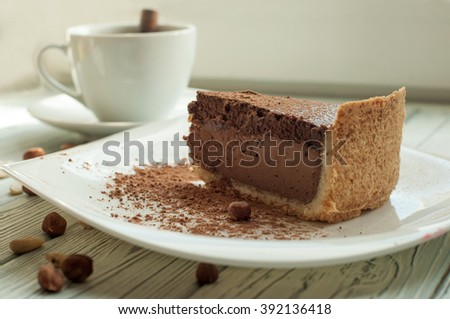 A composition with a cup of black coffee and a peace of a chocolate cheese cake decorated with cocoa powder and nuts on a light wooden surface