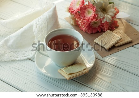 A composition with a cup of tea, several biscuits with butter, a lace napkin and a bouquet of  spring flowers on a white wooden surface - stock photo