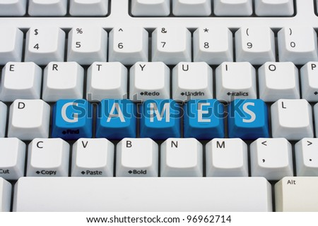 A computer keyboard with blue keys spelling games, Playing computer games - stock photo