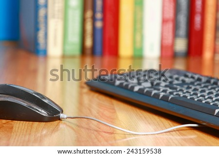 A computer mouse and a keyboard against books on the desk - stock photo