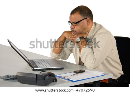 a concentrated working mature African-American businessman in front of his laptop and receiving bad news online, isolated on white background - stock photo