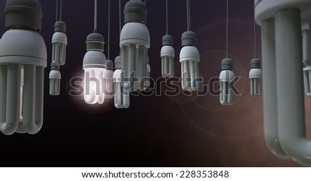 A concept image showing unlit dangling fluorescent light bulbs with one shining brightly showing leadership and innovation on an isolated dark background - stock photo