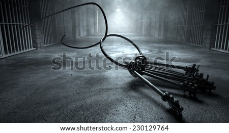 A concept of an eerie corridor at night showing jail cells dimly illuminated by various lights and a bunch of cell keys laying ominously on the floor being hooked by a bent wire coming from the cells - stock photo