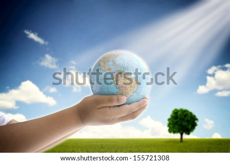 A conceptual image of a boy holding the earth globe with his two hand. A symbol of hope, future generation and  saving environment legacy for future generation.
