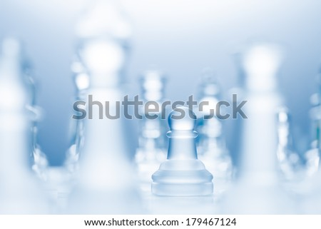 A conceptual photo of a transparent pawn made of glass on a chessboard. - stock photo