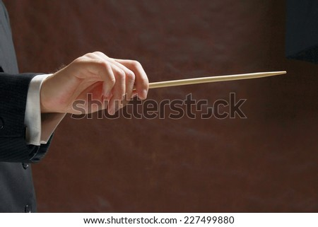 A concert conductor's hand with a baton, isolated on a black background - stock photo