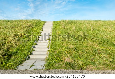 A concrete staircase between the grass of a dike on a sunny day in autumn. - stock photo