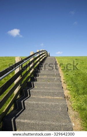 A concrete staircase with wooden banister between the green grass of a dike on a sunny day  - stock photo