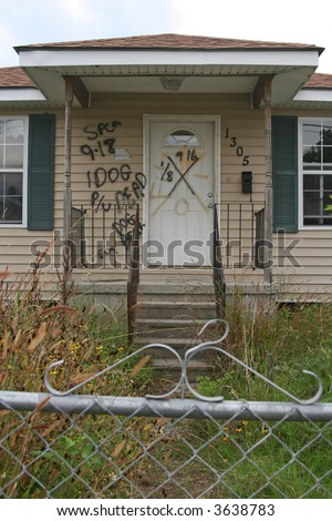 A condemned home in the 9th Ward of New Orleans, Louisiana, damaged in Hurricane Katrina. The writing indicates a dead dog was found in the home and needed to be picked up. - stock photo