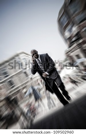A confident business man walking through the city while talking on his smartphone. Zoom blur vignetting and desaturated toning for added effect. - stock photo