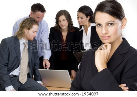 A confident businesswoman standing ahead of her team on white background