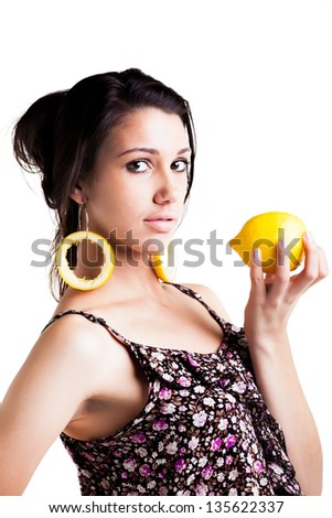 a confident caucasian young woman with dark brunette hair posing with round lemon skins attached to her earings and a full lemon in her hand