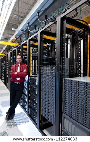 A confident datacenter manager looking at his datacenter equipment with a smile