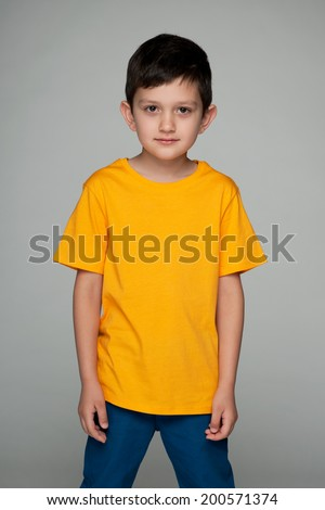 A confident fashion young boy in the yellow shirt against the gray background