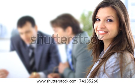 A confident relaxed business woman smiling with her colleagues at the back