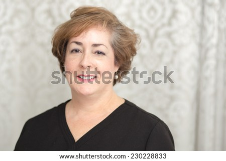 A confident smiling middle aged white woman with copy space on right.