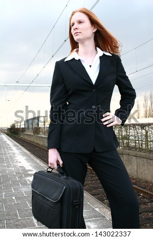 A confident young Caucasian business woman at a train station - waiting for the train.