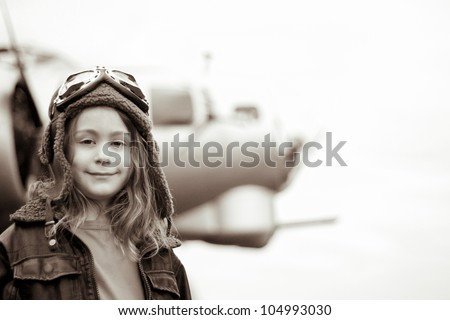 A confident young female pilot is gazing at the camera, wearing flight jacket / hat / goggles.  Bomber is visible in the background out of focus. - stock photo