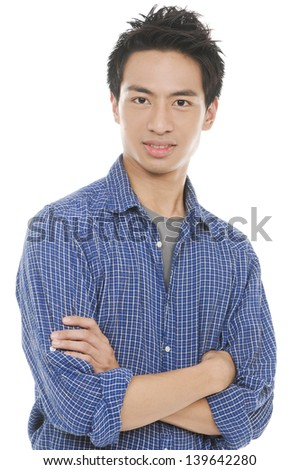 A confident young man stands with arms folded - stock photo