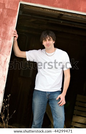A confident young model posing outside a barn.