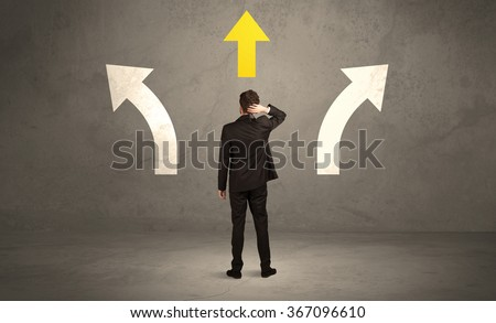 A confused businessman facing a grey urban wall with a yellow arrow pointing in the right direction concept - stock photo
