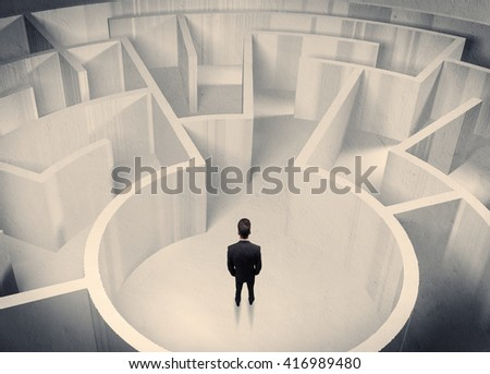 A confused businessman standing in the center of a maze surrounded with walls of the labyrinth - stock photo