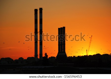 A construction crane silhouetted at sunset