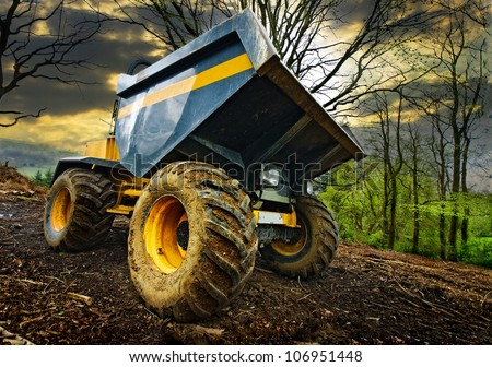 a construction dumper truck parked in the woods on a bit of a stormy looking day. A wide angle view from low down on the floor. - stock photo
