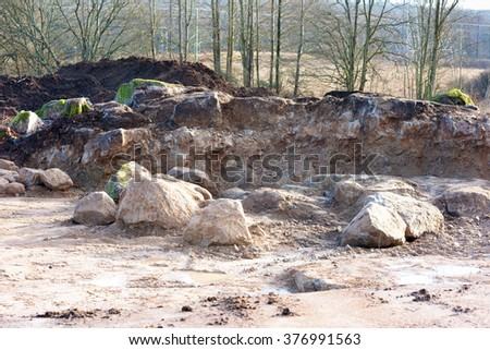 A construction site excavated down to bedrock. Large boulders lie on the ground. Soil is piled in the background close to some trees.