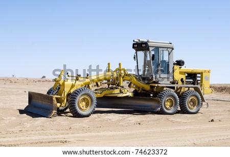 A construction vehicle flattening a field - stock photo