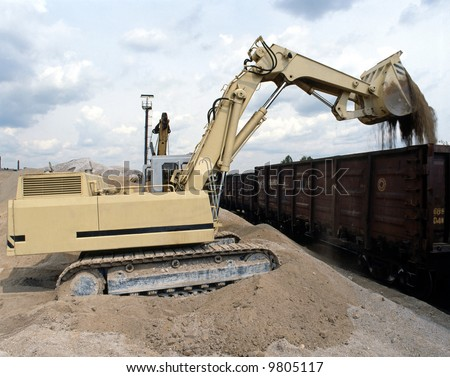A Construction vehicle loading gravel.