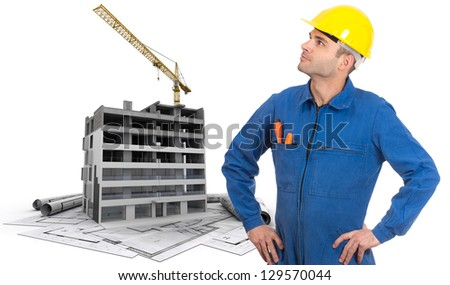 A construction worker, a building in construction and blueprints