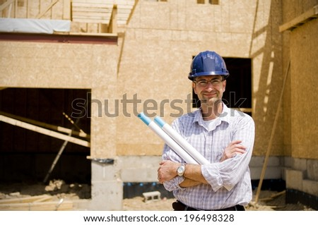 A construction worker and a partly built house. - stock photo