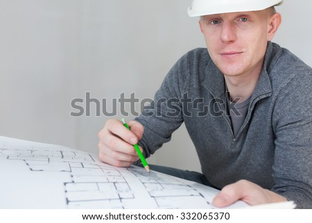A construction worker checking documents with pencil in his hand - stock photo