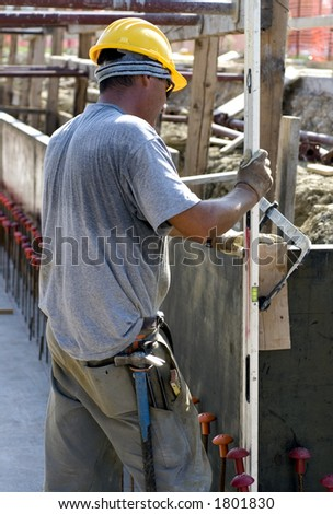 A construction worker checks the level of the forms prior to placing concrete.