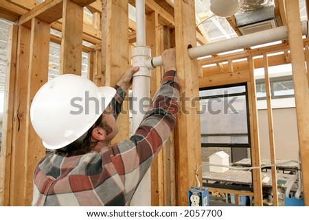 A construction worker connecting plumbing pipe in an unfinished wall. Focus is on the connecting pipes. - stock photo