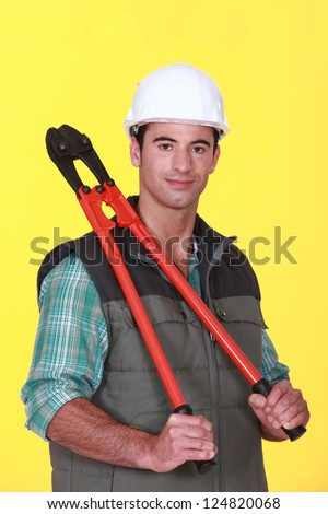 A construction worker holding pliers. - stock photo