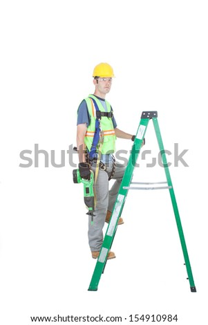 A construction worker in full safety kit climbs a fiberglass construction ladder. He has a power tool in his hands. Isolated on white. - stock photo