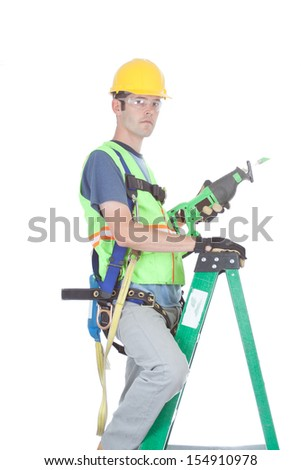A construction worker in full safety kit stands on a ladder holding a power tool. Isolated on white. - stock photo