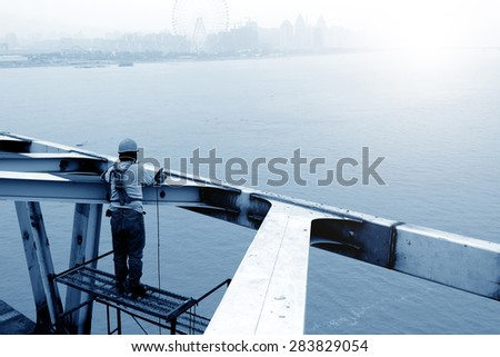 A construction worker in the repair of the bridge scaffolding - stock photo