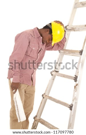 A construction worker leaning up against a ladder taking a break