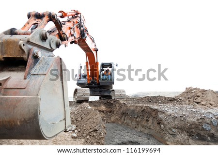 A construction worker operating a track hoe machine that is sitting on dirt with an isolated sky background. - stock photo