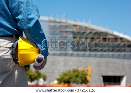 A construction worker or foreman at a construction site with blue prints and a hard hat - stock photo