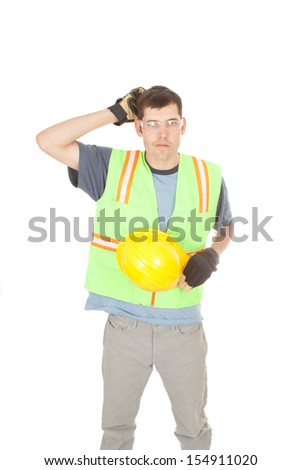 A construction worker removes his hard hat and scratches his head while wearing the rest of his safety gear. He looks confused. - stock photo